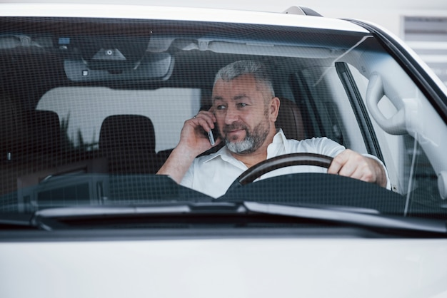Vista frontale. parlare di lavoro in macchina mentre è fermo. conversazione su nuove offerte Foto Gratuite