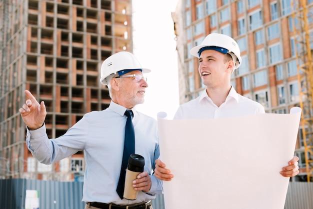 Vista frontale persone con progetto di costruzione e caffè Foto Gratuite