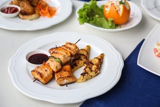 Vista frontale pollo alla griglia su spiedini con verdure e purè di patate su un piatto con salsa Foto Gratuite