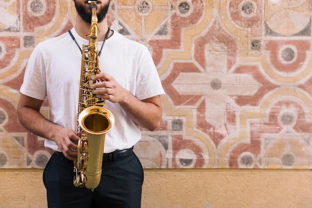 Vista frontale uomo che suona il sax con sfondo geometrico Foto Gratuite