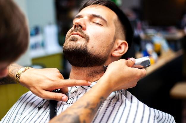 Vista frontale uomo ottenere una barba tagliata Foto Gratuite
