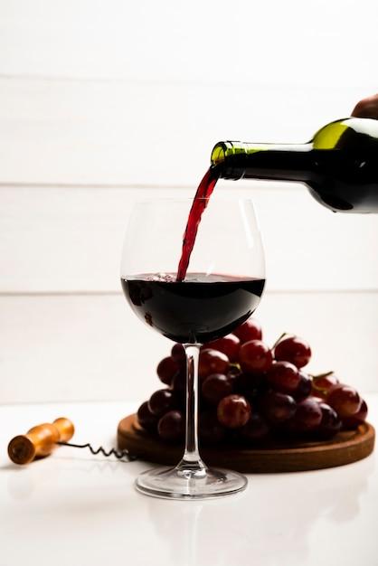 Vista frontale vino versato in un bicchiere Foto Gratuite