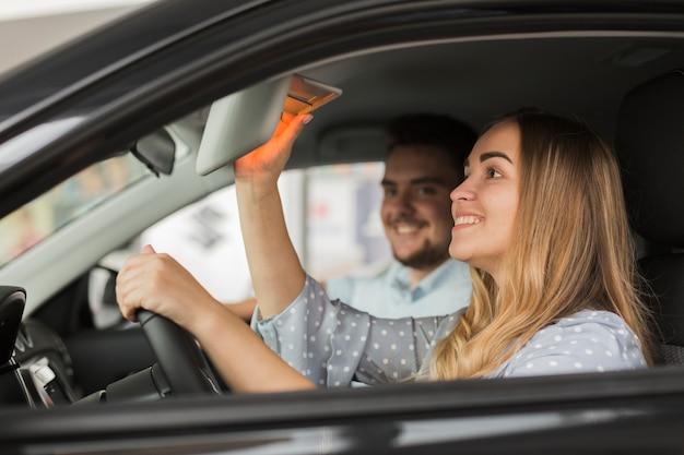 Vista laterale bella donna bionda in auto Foto Gratuite