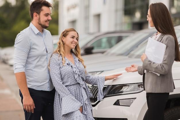 Vista laterale coppia parlando con un rivenditore di auto femminile Foto Gratuite