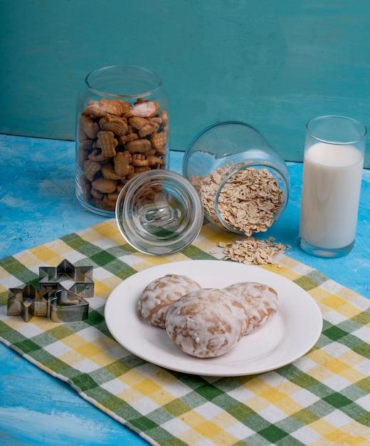 Vista laterale dei biscotti del pan di zenzero su un piatto bianco sul tavolo da cucina Foto Gratuite