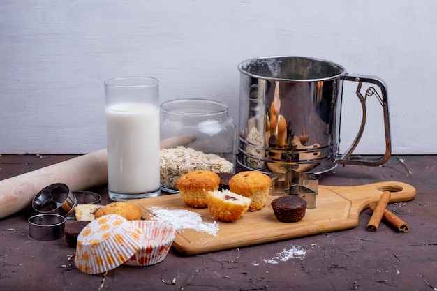 Vista laterale dei muffin e un bicchiere di latte su un tagliere di legno Foto Gratuite