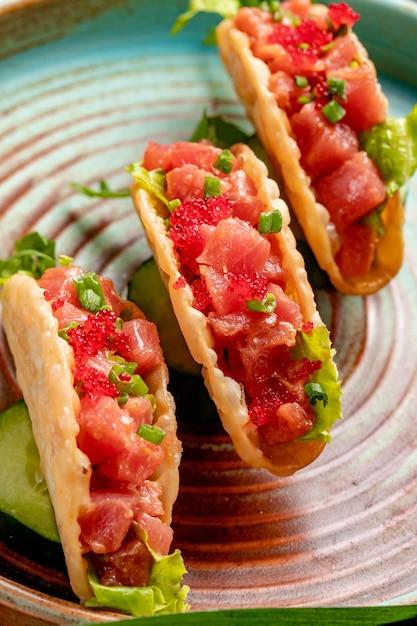 Vista laterale dei taci di color salmone con caviale rosso e cipolla verde su un piatto Foto Gratuite