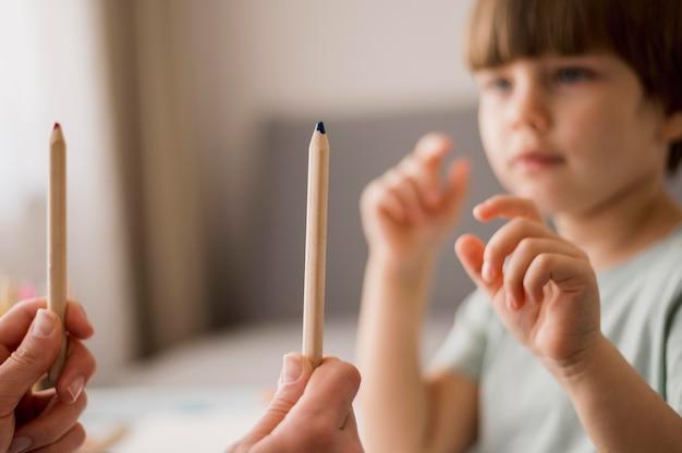 Vista laterale del bambino defocused che è istruito a casa Foto Gratuite