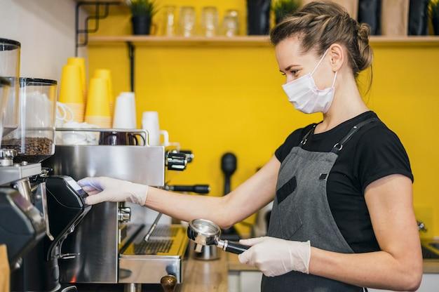 Vista laterale del barista femmina con guanti in lattice preparando il caffè per la macchina Foto Gratuite