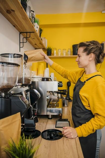 Vista laterale del barista femminile che macina il caffè Foto Gratuite