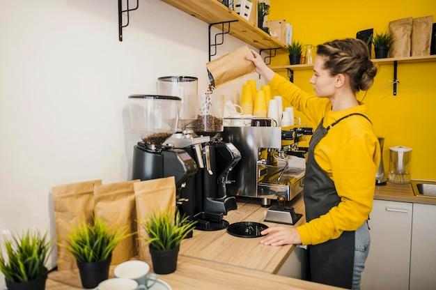 Vista laterale del barista macinare il caffè Foto Gratuite