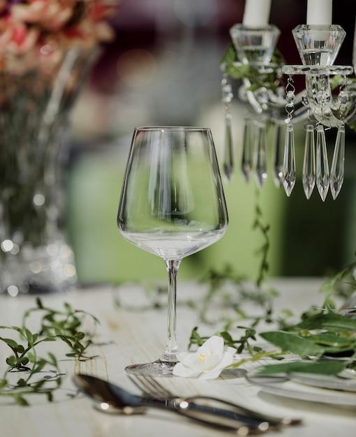 Vista laterale del bicchiere di vino vuoto sulla tavola di nozze Foto Gratuite