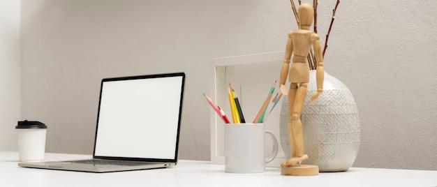 Vista laterale del computer portatile con tracciato di ritaglio sul tavolo bianco con cancelleria e decorazioni in ufficio a casa Foto Premium