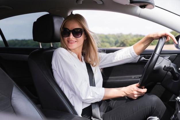 Vista laterale del conducente con occhiali da sole Foto Gratuite