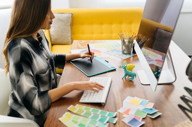 Vista laterale del graphic designer alla scrivania Foto Gratuite