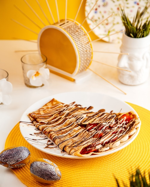 Vista laterale del pancake sottile con le fragole e le banane affettate coperte di salsa di cioccolato sul piatto bianco Foto Gratuite