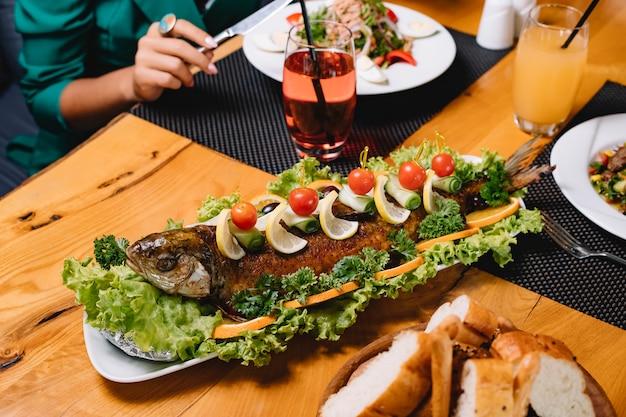 Vista laterale del pane al pomodoro del limone della lattuga di pesce arrostita Foto Gratuite