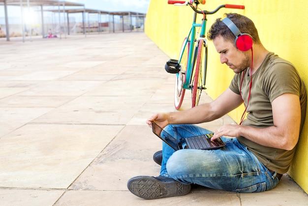 Vista laterale del ragazzo attraente è seduto sul pavimento Foto Premium