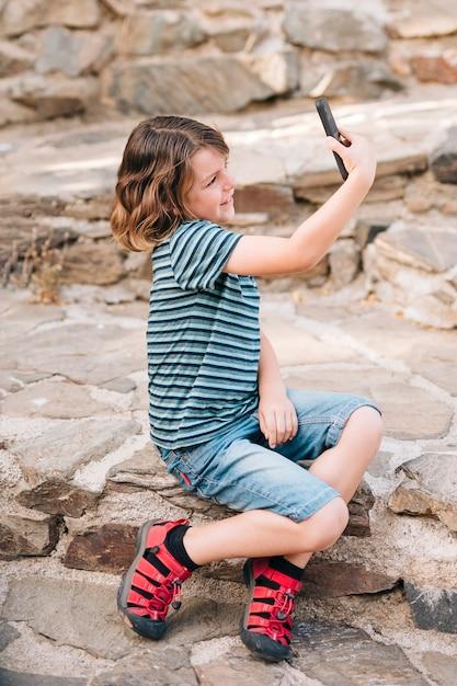 Vista laterale del ragazzo che prende un selfie Foto Gratuite