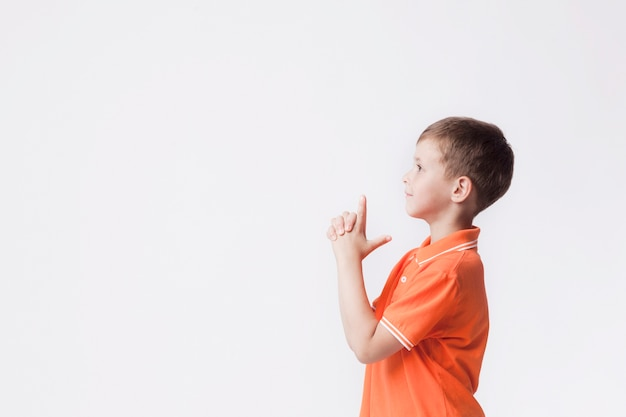 Vista laterale del ragazzo con il gesto della pistola che gioca contro il fondo bianco Foto Gratuite