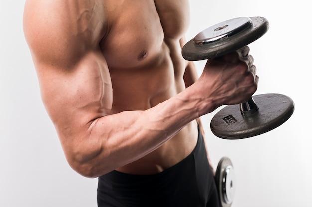 Vista laterale del torso atletico dell'uomo che tiene i pesi Foto Gratuite