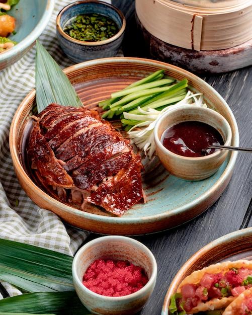 Vista laterale dell'anatra di pechino asiatica tradizionale dell'alimento con i cetrioli e la salsa su un piatto Foto Gratuite