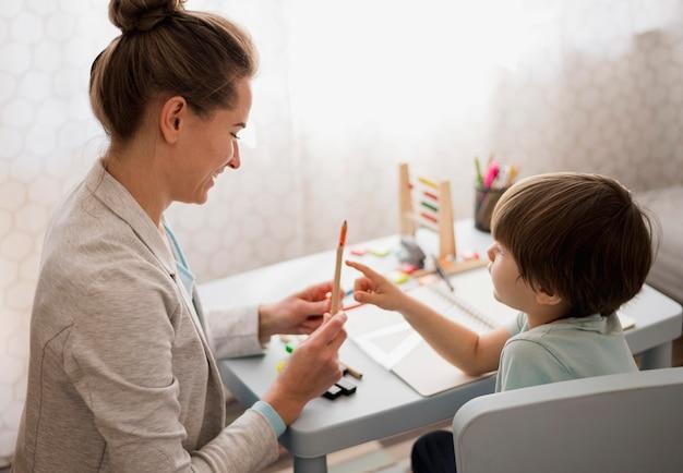 Vista laterale dell'apprendimento a casa del tutor e del bambino Foto Gratuite