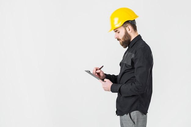 Vista laterale dell'architetto maschio che indossa la scrittura gialla dell'elmetto protettivo sulla lavagna per appunti Foto Gratuite