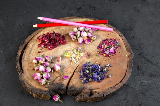 Vista laterale dell'assortimento del fiore asciutto e del tè rosa con due matite sul bordo di legno sul nero Foto Gratuite