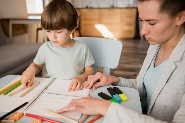 Vista laterale dell'insegnante femminile che insegna al bambino a casa Foto Gratuite