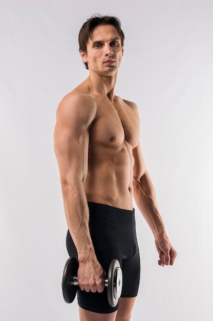 Vista laterale dell'uomo atletico senza camicia che tiene peso Foto Gratuite