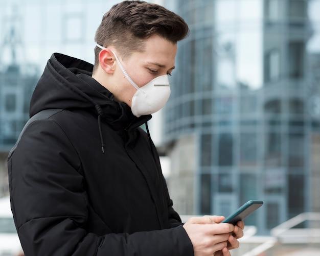 Vista laterale dell'uomo che esamina il suo telefono mentre indossa una maschera medica Foto Gratuite