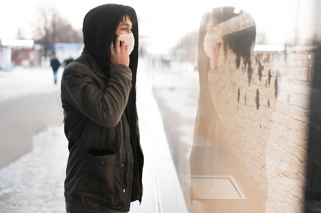 Vista laterale dell'uomo che parla al telefono mentre indossa una maschera medica fuori Foto Gratuite