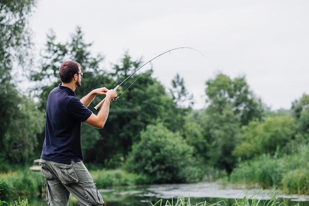 Vista laterale dell'uomo che pesca nel lago Foto Gratuite
