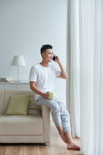 Vista laterale dell'uomo che si appollaia sul bracciolo del divano parlando al telefono e guardando nella finestra Foto Gratuite