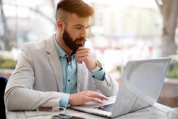 Vista laterale dell'uomo in vestito che controlla i email sul computer portatile Foto Premium