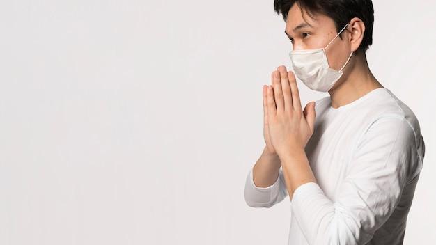 Vista laterale dell'uomo malato con pregare medico della maschera Foto Gratuite