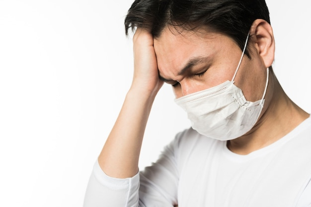 Vista laterale dell'uomo triste con coronavirus che indossa una maschera medica Foto Gratuite