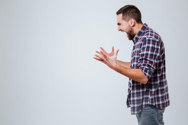 Vista laterale dell'uomo urlando barbuto in camicia Foto Gratuite