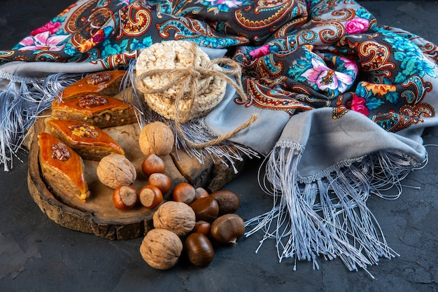 Vista laterale della baklava con noci intere e pani di riso sullo scialle con fiocco Foto Gratuite