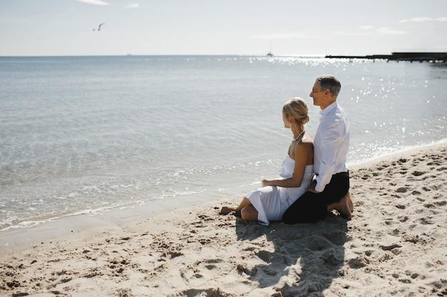 Vista laterale della coppia che è seduta sulla spiaggia di sabbia vicino al mare e si affaccia sul paesaggio mozzafiato Foto Gratuite