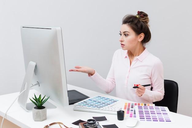 Vista laterale della donna alla scrivania guardando il computer e non capendo cosa è successo Foto Gratuite