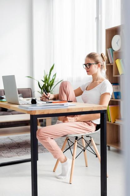 Vista laterale della donna allo scrittorio che funziona mentre a casa Foto Gratuite