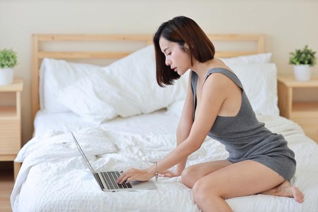 Vista laterale della donna asiatica indipendente adulta che lavora al computer e al telefono cellulare sul letto in camera da letto Foto Premium