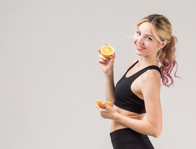 Vista laterale della donna atletica di smiley che propone con gli aranci Foto Gratuite