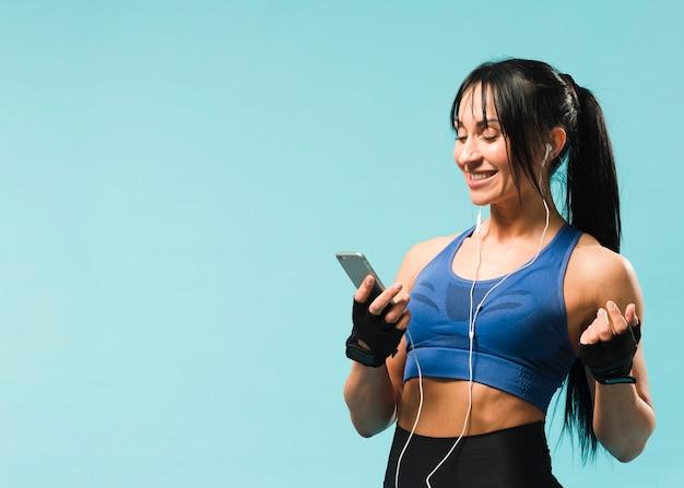 Vista laterale della donna atletica in attrezzatura della palestra che gode della musica Foto Gratuite