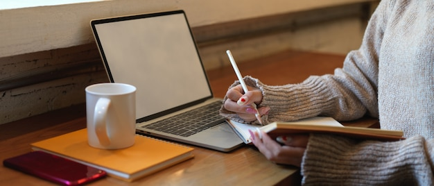 Vista laterale della donna che scrive nessun taccuino in bianco mentre posa al tavolo da lavoro in legno con mock up laptop e smartphone Foto Premium