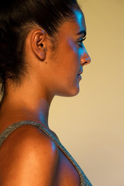 Vista laterale della donna con sfondo giallo Foto Gratuite