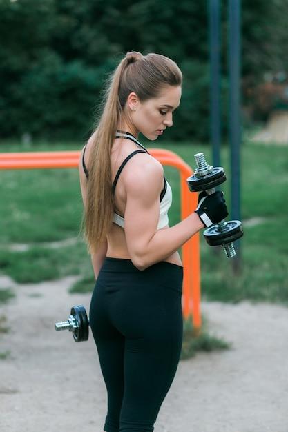 Vista laterale della donna in forma sollevamento manubri per armi formazione nel parco Foto Gratuite