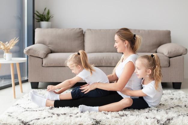 Vista laterale della famiglia felice della madre e delle figlie a casa Foto Gratuite
